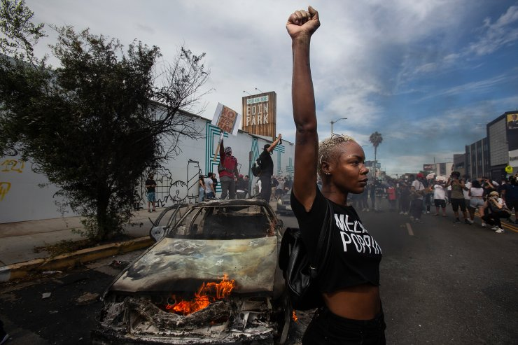 A protester raises her fist in the air next to a burning police vehicle in Los Angeles, May 30, 2020, during a demonstration over the death of George Floyd. The image was part of a series of photographs by The Associated Press that won the 2021 Pulitzer Prize for breaking news photography. AP