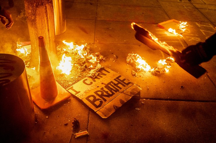 A Black Lives Matter protester burns a sign outside the Mark O. Hatfield United States Courthouse on July 21, 2020 in Portland, Ore. The image was part of a series of photographs by The Associated Press that won the 2021 Pulitzer Prize for breaking news photography. AP
