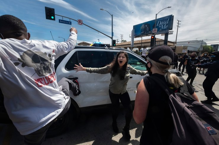 A protester, center, tries to stop others from attacking a police vehicle during a protest over the death of George Floyd in Los Angeles, May 30, 2020. The image was part of a series of photographs by The Associated Press that won the 2021 Pulitzer Prize for breaking news photography. AP