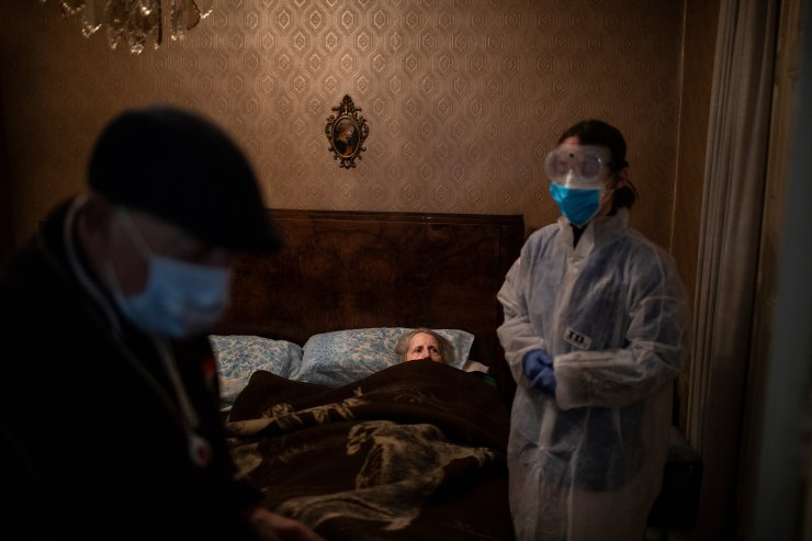 Josefa Ribas, 86, who is bedridden, looks at nurse Alba Rodriguez as Ribas' husband, Jose Marcos, 89, stands by in their home in Barcelona, Spain, March 30, 2020, during the coronavirus outbreak. Ribas suffers from dementia, and Marcos fears for them both if the virus enters their home. 'If I get the virus, who will take care of my wife?' The image was part of a series by Associated Press photographer Emilio Morenatti that won the 2021 Pulitzer Prize for feature photography. AP