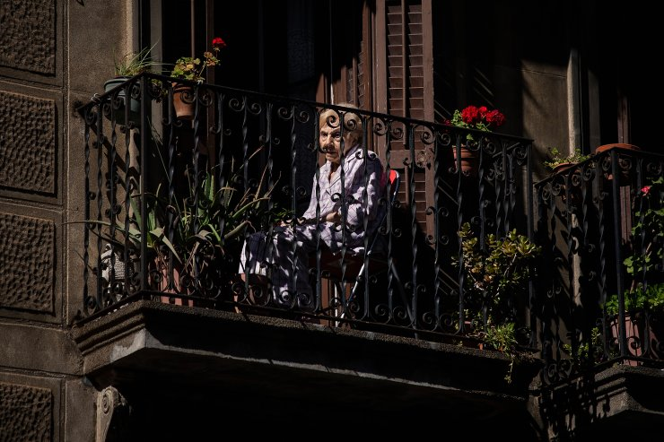 A woman sits on her balcony in downtown Barcelona, Spain, May 7, 2020. The image was part of a series by Associated Press photographer Emilio Morenatti that won the 2021 Pulitzer Prize for feature photography. AP