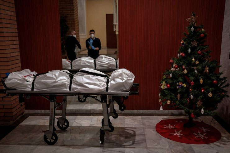 Mortuary workers take off their protective clothing at the entrance of a building decorated with a Christmas tree, after removing the body of person who is suspected of dying from COVID-19 in Barcelona, Spain, Dec. 23, 2020. The image was part of a series by Associated Press photographer Emilio Morenatti that won the 2021 Pulitzer Prize for feature photography. AP