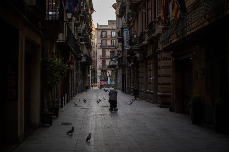 A woman pushes a cart with her belongings as she walks along an empty street in downtown Barcelona, Spain, March 21, 2020. The image was part of a series by Associated Press photographer Emilio Morenatti that won the 2021 Pulitzer Prize for feature photography. AP