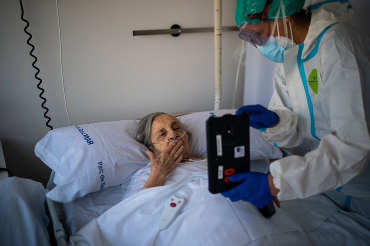 Nurse Marta Fernandez holds up a tablet computer over the chest of 94-year-old Maria Teresa Argullos Bove so that she can speak to her sister, children and grandchildren from her hospital bed at the COVID-19 ward at the hospital del Mar in Barcelona, Spain, Nov. 18, 2020. The image was part of a series by Associated Press photographer Emilio Morenatti that won the 2021 Pulitzer Prize for feature photography. AP