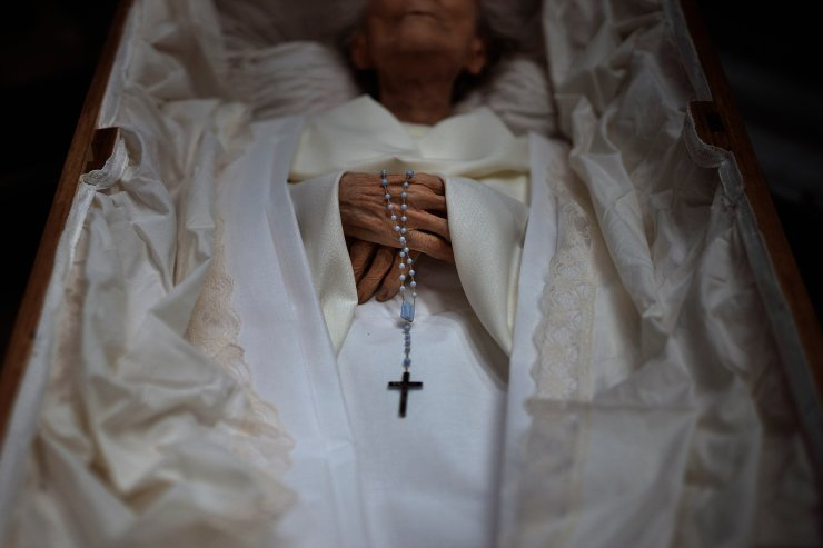 The body of an elderly person is prepared inside a coffin for her funeral at a morgue in Barcelona, Spain, Nov. 5, 2020. The image was part of a series by Associated Press photographer Emilio Morenatti that won the 2021 Pulitzer Prize for feature photography. AP