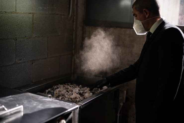 A mortuary worker collects the ashes of a COVID-19 victim from an oven after the remains where cremated at Memora mortuary in Girona, Spain, Nov. 19, 2020. The image was part of a series by Associated Press photographer Emilio Morenatti that won the 2021 Pulitzer Prize for feature photography. AP