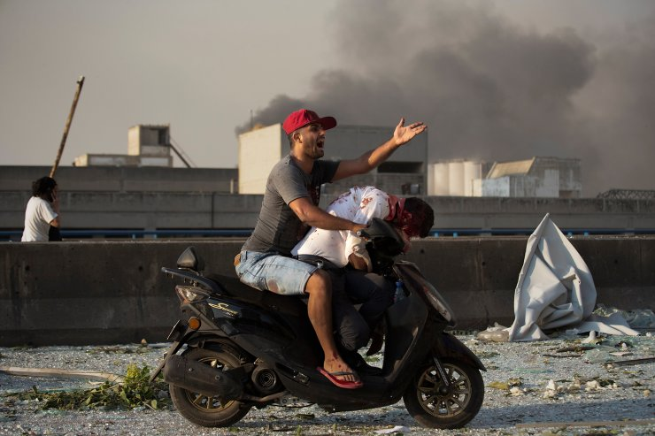 A man evacuates an injured person after a massive explosion in Beirut, Lebanon, Aug. 4, 2020. The image was part of a series of photographs by The Associated Press that was a finalist for the 2021 Pulitzer Prize for breaking news photography.  AP