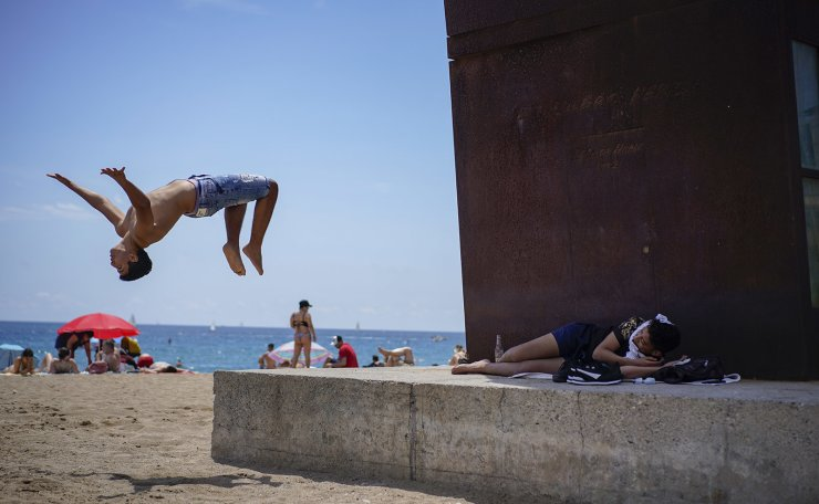 A boy does a back flip at Barcelona's beach, Spain, Sunday, June 27, 2021. Almost a year after face masks became mandatory indoors and outdoors in Spain, people from Saturday are no longer required to wear them outside as long as they can stay at least 1.5 meters (5 feet) apart. AP