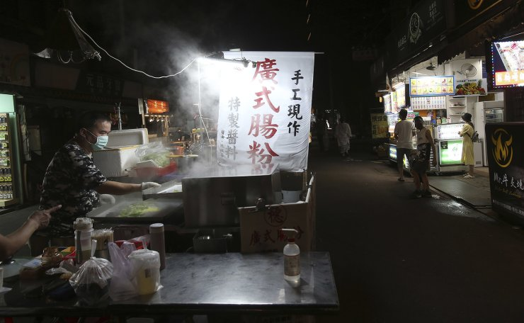 People wear face masks to protect against the spread of the coronavirus at a no on-site eating and drinking night market after the COVID-19 alert raise to level 3 in Taipei, Taiwan, Tuesday, June 29, 2021. AP