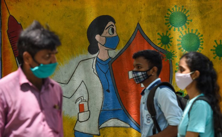 Residents walk past a wall mural depicting a health worker wearing a facemask while holding a vaccine and a shield to spread awareness about the Covid-19 coronavirus, in Mumbai on June 30, 2021. AFP