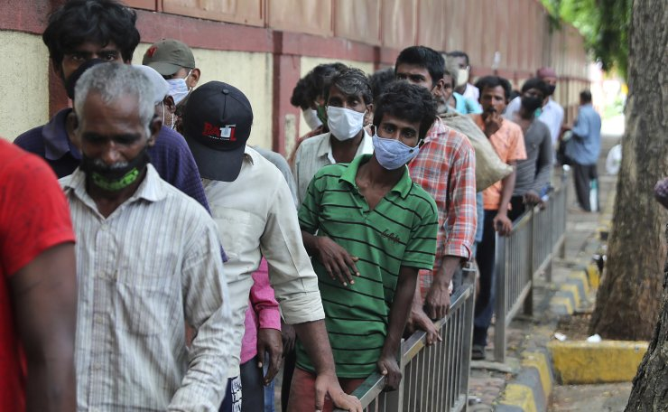People wearing face masks as a precaution against the coronavirus line up to receive free food distributed by a volunteer in Mumbai, India, Wednesday, June 30, 2021. AP