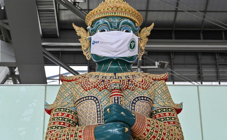 A traditional Thai statue wears a face mask as a campaign for travellers to prevent the spread of Covid-19 coronavirus at the departure terminal of Suvarnabhumi Airport in Bangkok on June 30, 2021. AFP