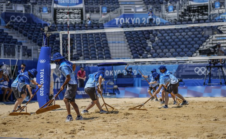 Volunteers prepare the centre court during a women's beach volleyball against at the 2020 Summer Olympics, Saturday, July 24, 2021, in Tokyo, Japan. AP