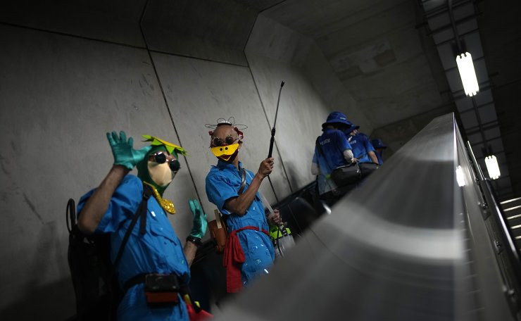 Volunteers wearing masks wave as they carry spray canisters of water, that they use to cool down fans, inside the Fuji International Speedway, the finish for the women's cycling road race that is underway, at the 2020 Summer Olympics, Sunday, July 25, 2021, in Oyama, Japan. AP