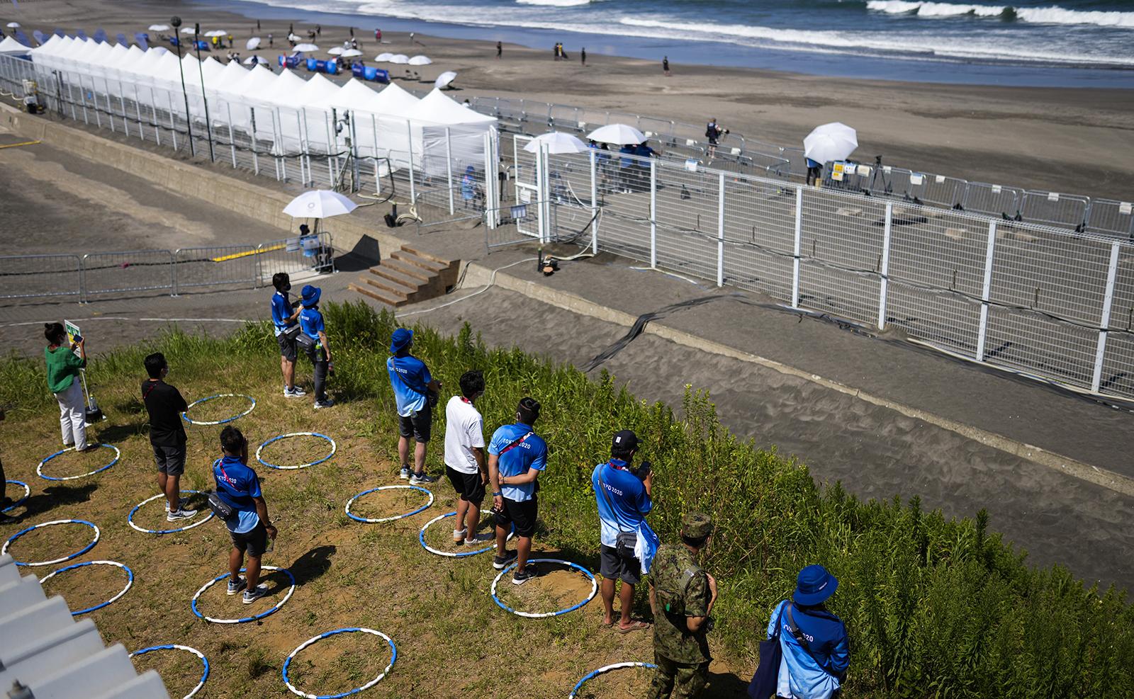 Volunteers keep social distance as they watch surfing at the 2020 Summer Olympics, Sunday, July 25, 2021, at Tsurigasaki beach in Ichinomiya, Japan. AP