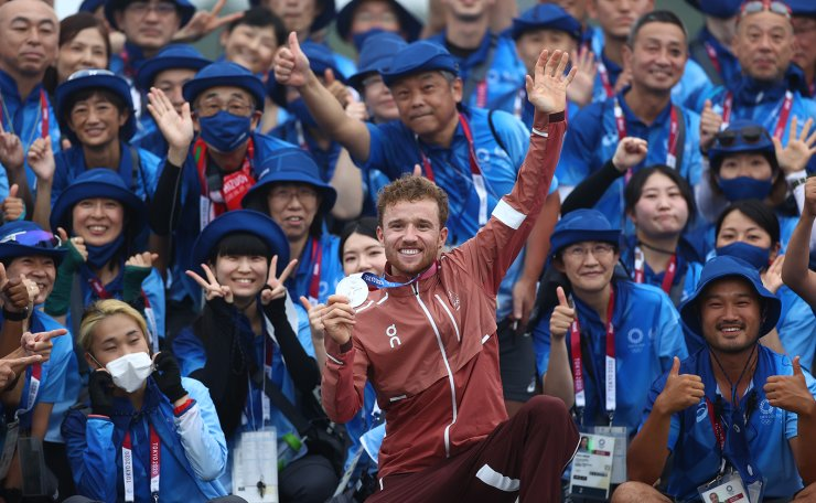 Tokyo 2020 Olympics - Mountain Bike - Men's Cross Country - Medal Ceremony - Izu MTB Course - Shizuoka, Japan - July 26, 2021.  Silver medallist Mathias Fluckiger of Switzerland celebrates with volunteers after the race. REUTERS