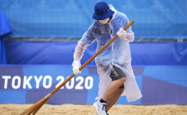 A member of the grounds crew rakes the sand before a men's beach volleyball match at the 2020 Summer Olympics, Tuesday, July 27, 2021, in Tokyo, Japan. AP