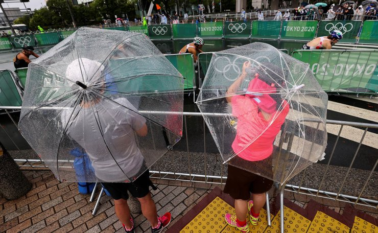 Tokyo 2020 Olympics - Triathlon - Women's Olympic Distance - Final - Odaiba Marine Park, Tokyo, Japan July 27, 2021. Fans and residents try to catch a glimpse of the women's triathlon event in the rain caused by tropical storm Nepartak. REUTERS