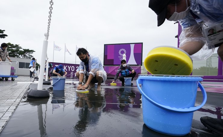 Volunteers attempt to remove the rainwater from the range before the women's trap practice at the Asaka Shooting Range in the 2020 Summer Olympics, Tuesday, July 27, 2021, in Tokyo, Japan. AP