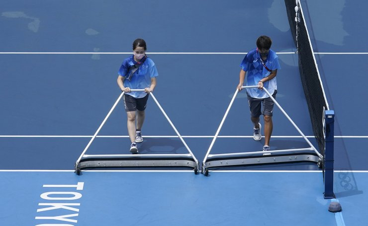 Volunteers work to dry a tennis court before the start of the tennis matches at the 2020 Summer Olympics, Tuesday, July 27, 2021, in Tokyo, Japan. AP