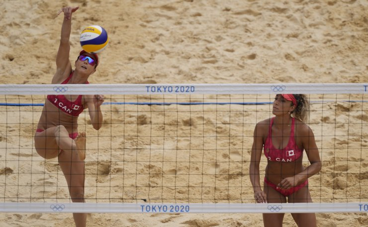 Heather Bansley, left, of Canada, returns a shot as teammate Brandie Wilkerson looks on during a women's beach volleyball match against Argentina at the 2020 Summer Olympics, Tuesday, July 27, 2021, in Tokyo, Japan. AP