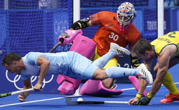 Argentina's Lucas Martin Vila (12) battles with Australia's Jeremy Thomas Hayward (32) on a scoring attempt on goalkeeper Andrew Lewis Charter (30) during a men's field hockey match against Australia at the 2020 Summer Olympics, Tuesday, July 27, 2021, in Tokyo, Japan. AP