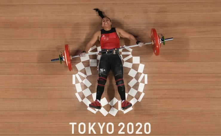 Sema Nancy Ludrick Rivas of Nicaragua lies on the ground after an unsuccessful attempt as she competes in the women's 64kg weightlifting event, at the 2020 Summer Olympics, Tuesday, July 27, 2021, in Tokyo, Japan. AP