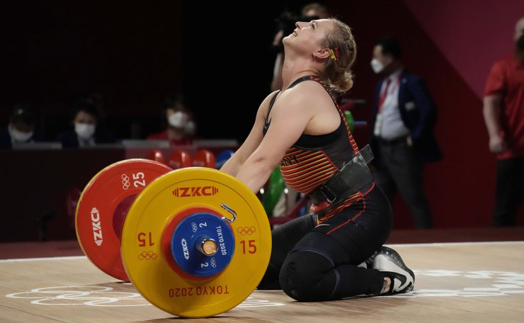 Sabine Beate Kusterer of Germany reacts after an unsuccessful attempt as she competes in the women's 59kg weightlifting event, at the 2020 Summer Olympics, Tuesday, July 27, 2021, in Tokyo, Japan. AP