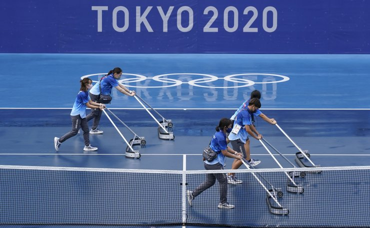 Workers push water off of a court during a rain delay in the tennis competition at the 2020 Summer Olympics, Tuesday, July 27, 2021, in Tokyo, Japan. AP
