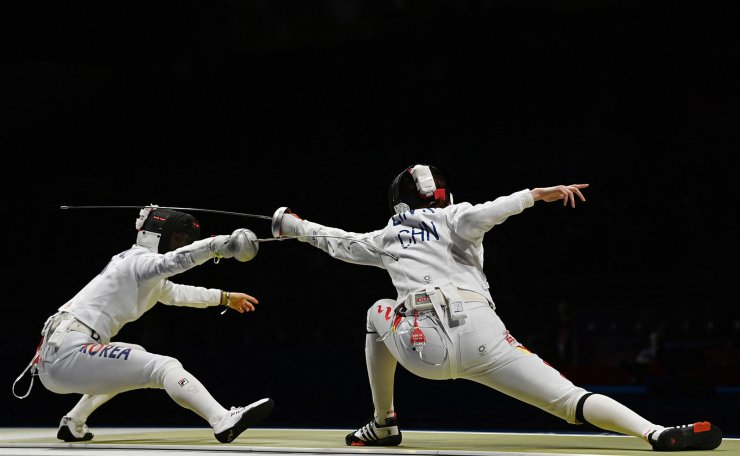South Korea's Choi Injeong (L) compete against China's Lin Sheng  in the women?s team epee semi-final bout during the Tokyo 2020 Olympic Games at the Makuhari Messe Hall in Chiba City, Chiba Prefecture, Japan, on July 27, 2021. AFP