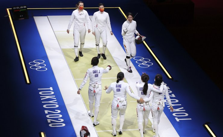 Tokyo 2020 Olympics - Fencing - Women's Team Epee - Semifinal - Makuhari Messe Hall B - Chiba, Japan - July 27, 2021. Song Sera of South Korea, Choi In-Jeong of South Korea, Lee Hye In of South Korea and Song Sera of South Korea celebrate after competing as members of Team China look on. REUTERS