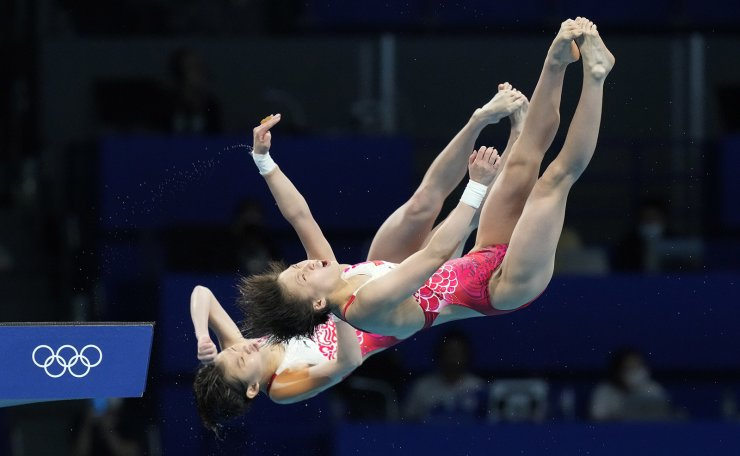 Yuxi Chen and Jiaqi Zhang of China compete during the women's synchronized 10m platform diving final at the Tokyo Aquatics Centre at the 2020 Summer Olympics, Tuesday, July 27, 2021, in Tokyo, Japan. AP