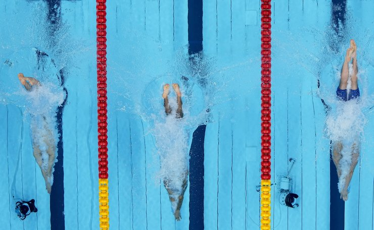 Caeleb Dressel, of the United States, is flanked by Alessandro Miressi, of Italy, and Hwang Sunwoo, of South Korea, as they swim in a men's 100-meter freestyle semifinal at the 2020 Summer Olympics, Wednesday, July 28, 2021, in Tokyo, Japan. AP