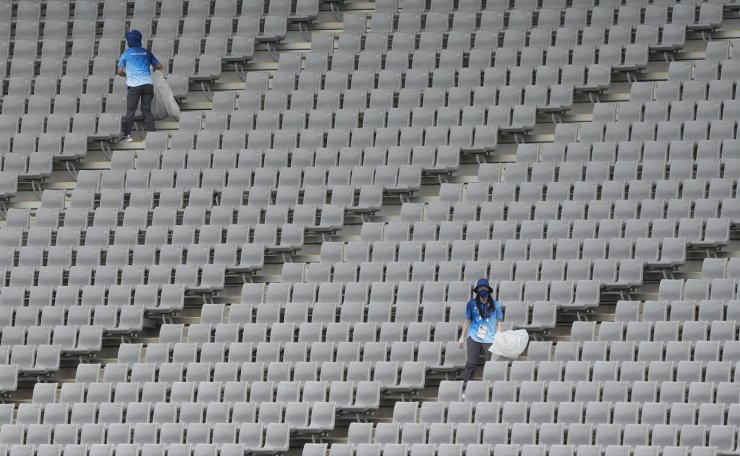 Volunteers clean empty stands during the men's rugby sevens 9-10 placing match between Kenya and Ireland at the 2020 Summer Olympics, Wednesday, July 28, 2021 in Tokyo, Japan. AP