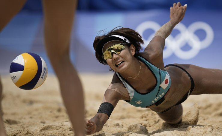 Miki Ishi, of Japan, dives for the ball during a women's beach volleyball match against Switzerland at the 2020 Summer Olympics, Wednesday, July 28, 2021, in Tokyo, Japan. AP
