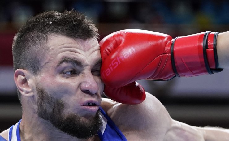 Russian Olympic Committee's Imam Khataev receives a punch from Kazakhstan's Bekzad Nurdauletov during the men's light heavyweight 81-kg preliminaries boxing match at the 2020 Summer Olympics, Wednesday, July 28, 2021, in Tokyo, Japan. AP