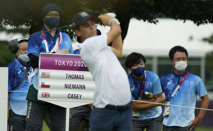 Volunteers follow the Chile's Joaquin Niemann tee shot on the fourth hole during the first round of the men's golf event at the 2020 Summer Olympics on Wednesday, July 28, 2021, at the Kasumigaseki Country Club in Kawagoe, Japan. AP