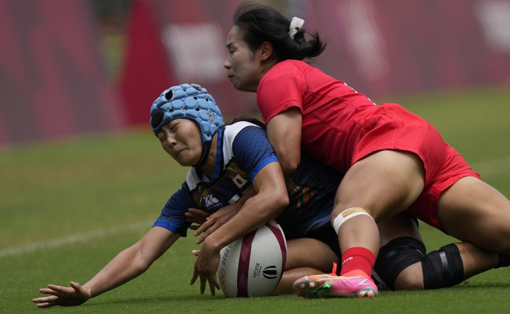 Japan's Yume Hirano, left, is tackled by China's Yang Feifei, in their women's rugby sevens match at the 2020 Summer Olympics, Friday, July 30, 2021 in Tokyo, Japan. AP