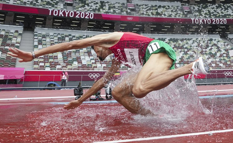 Mohamed Tindouft, of Morocco, falls during his heat of the men's 3,000-meter steeplechase at the 2020 Summer Olympics, Friday, July 30, 2021, in Tokyo. AP