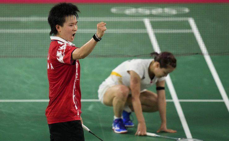 China's He Bing Jiao, left, celebrate after she winning against Japan's Nozomi Okuhara, right, during their women's singles badminton quarterfinal match at the 2020 Summer Olympics, Friday, July 30, 2021, in Tokyo, Japan. AP