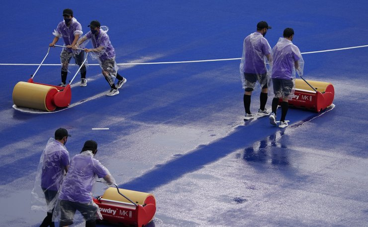Workers remove excess water from the pitch before starting a delayed women's field hockey match between Germany and South Africa at the 2020 Summer Olympics, Friday, July 30, 2021, in Tokyo, Japan. AP
