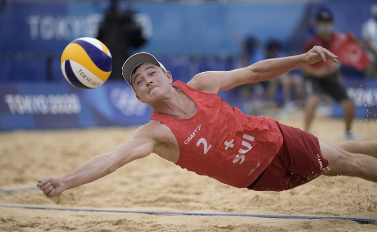 Mirco Gerson, of Switzerland, dives for the ball during a men's beach volleyball match against Italy at the 2020 Summer Olympics, Friday, July 30, 2021, in Tokyo, Japan. AP