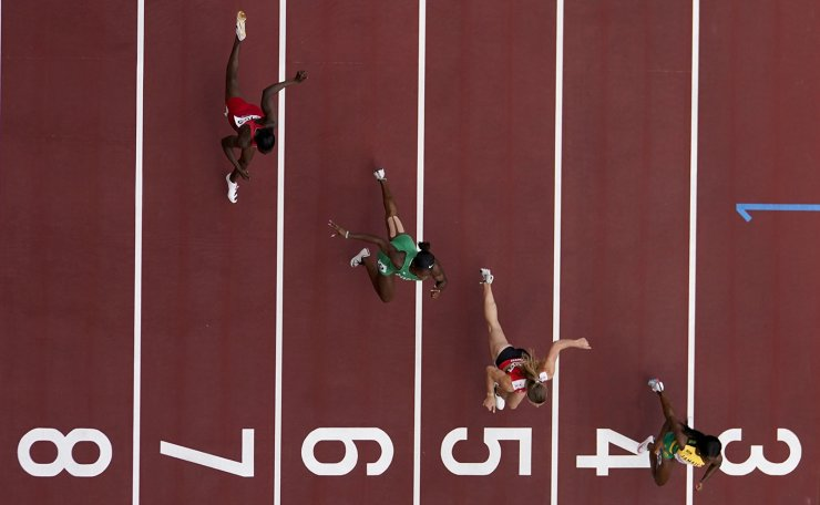 Shelly-Ann Fraser-Pryce, of Jamaica, Ajla Del Ponte, of Switzerland, Nzubechi Nwokocha, of Nigeria, and Gina Bass, of Gambia, compete during the first round of the women's 100-meter the 2020 Summer Olympics, Friday, July 30, 2021, in Tokyo. AP