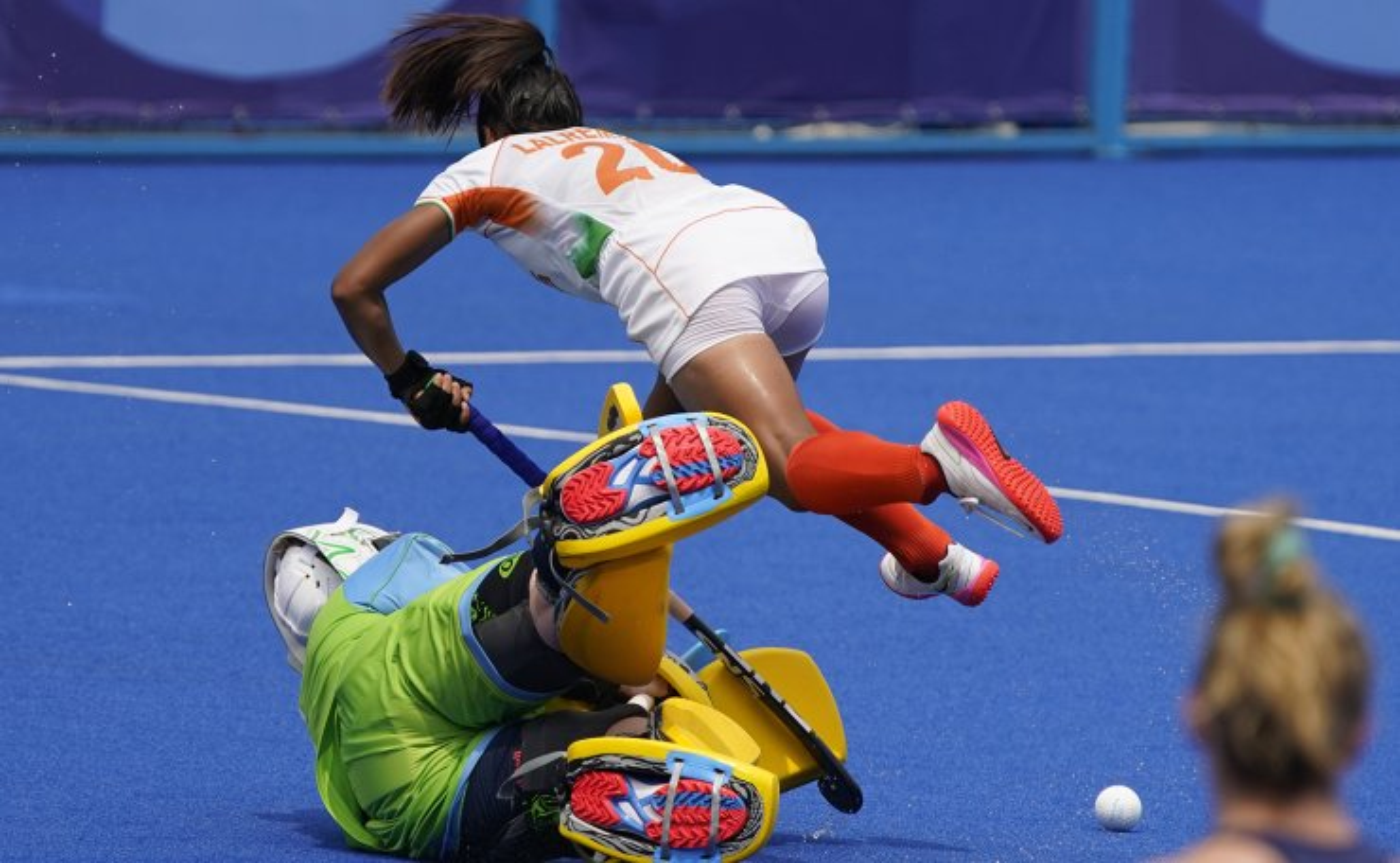 India forward Lalremsiami (20) falls over Ireland goalkeeper Ayeisha McFerran (1) during a women's field hockey match at the 2020 Summer Olympics, Friday, July 30, 2021, in Tokyo, Japan. AP