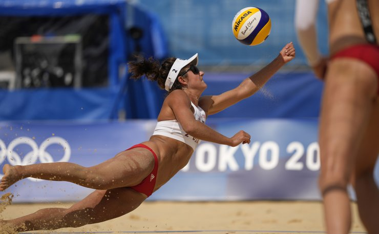 Sarah Sponcil, of the United States, dives for the ball during a women's beach volleyball match against Brazil at the 2020 Summer Olympics, Saturday, July 31, 2021, in Tokyo, Japan. AP