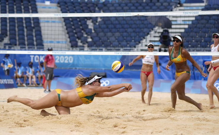 Rebecca Silva, bottom, of Brazil, dives for the ball as teammate Ana Patricia Silva Ramos, second from right, watches during a women's beach volleyball match against at the 2020 Summer Olympics, Saturday, July 31, 2021, in Tokyo, Japan. AP