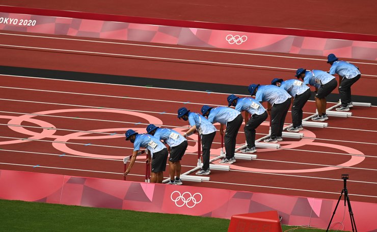 Staff set hurdles ahead of the women's 100m hurdles heats during the Tokyo 2020 Olympic Games at the Olympic Stadium in Tokyo on July 31, 2021. AFP