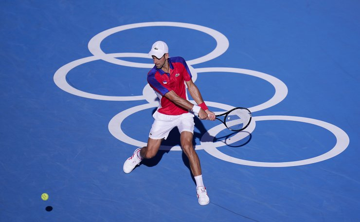 Novak Djokovic, of Serbia, returns a shot to Pablo Carreno Busta, of Spain, during the bronze medal match of the tennis competition at the 2020 Summer Olympics, Saturday, July 31, 2021, in Tokyo, Japan. AP