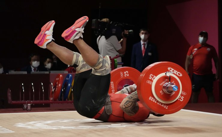Arley Mendez Perez of Chile falls as he ccompetes in the men's 81kg weightlifting event, at the 2020 Summer Olympics, Saturday, July 31, 2021, in Tokyo, Japan. AP