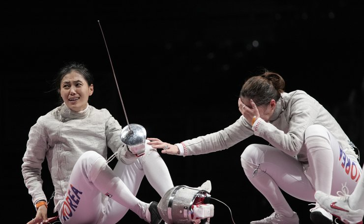 Kim Jiyeon of South Korea, left, celebrate defeating Rossella Gregorio of Italy and won the women's Sabre team bronze medal competition at the 2020 Summer Olympics, Saturday, July 31, 2021, in Chiba, Japan. AP